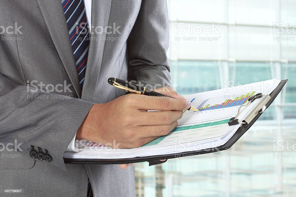 A man writing with a ballpoint pen on a chart on a clipboard stock photo