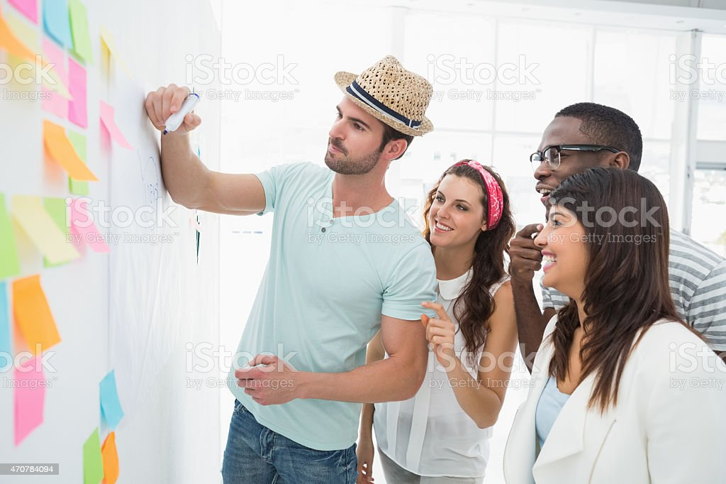 Man writing with marker and presenting at his colleagues stock photo
