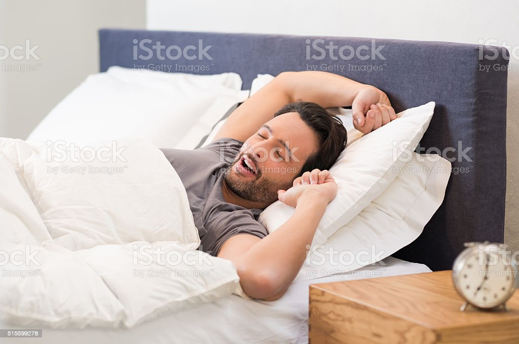 Man yawns in bed stock photo