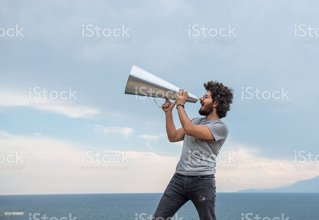 Man yelling trough a megaphone in outdoor stock photo