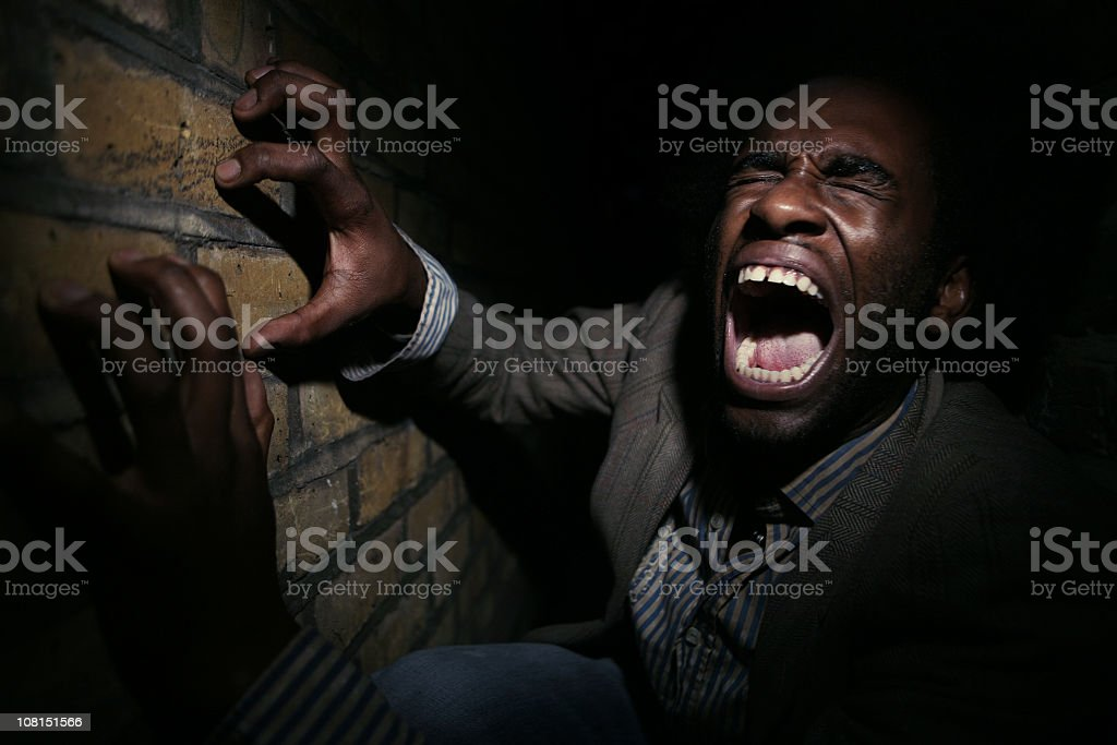 Man yelling while clawing a brick wall royalty-free stock photo