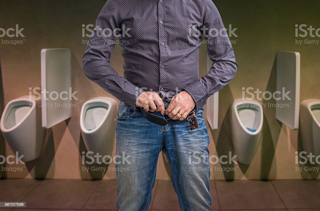 Man zip his pants up after peeing on the toilet stock photo