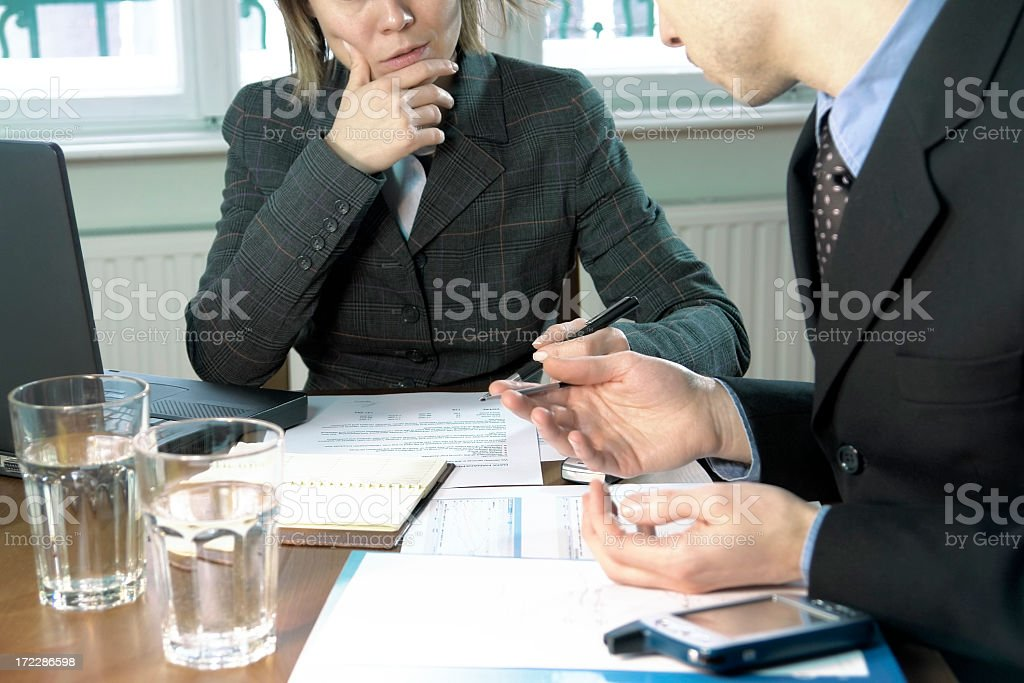 Management team discussing schema, chart lying on desk, home interior royalty-free stock photo