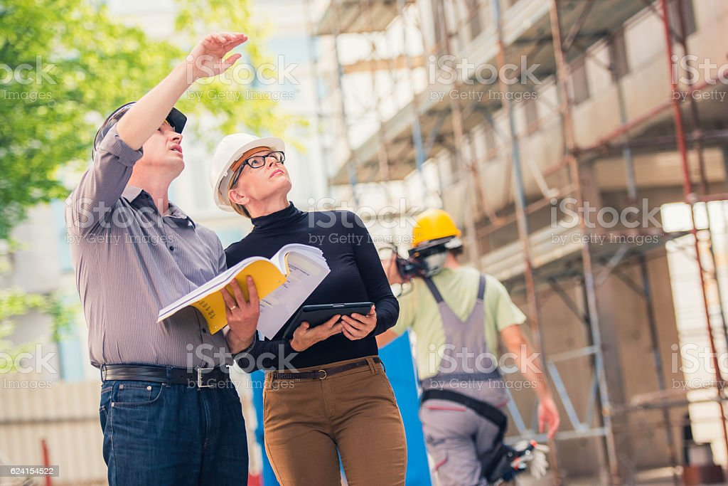 Manager and architect discussing construction progress stock photo
