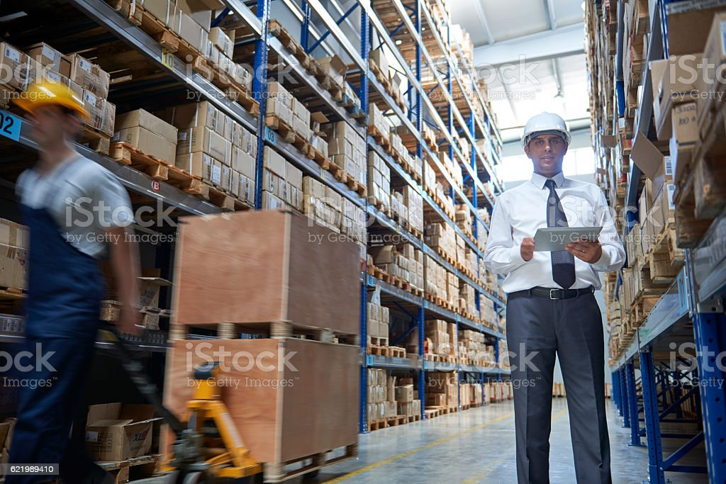 Manager and coworker in warehouse aisle stock photo