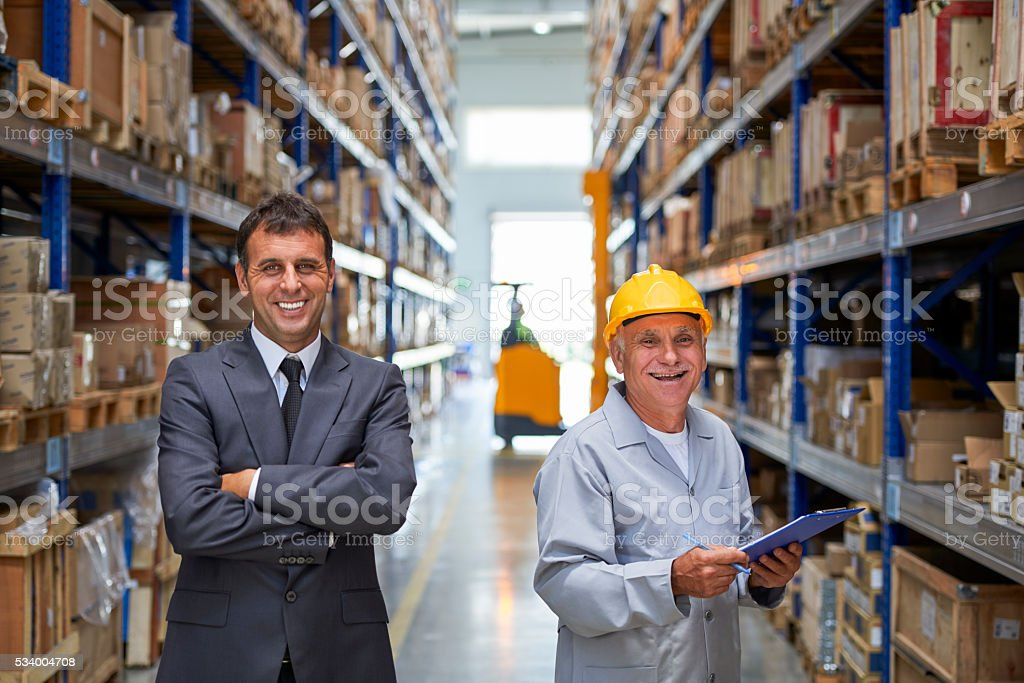 Manager and coworker standing in warehouse aisle stock photo