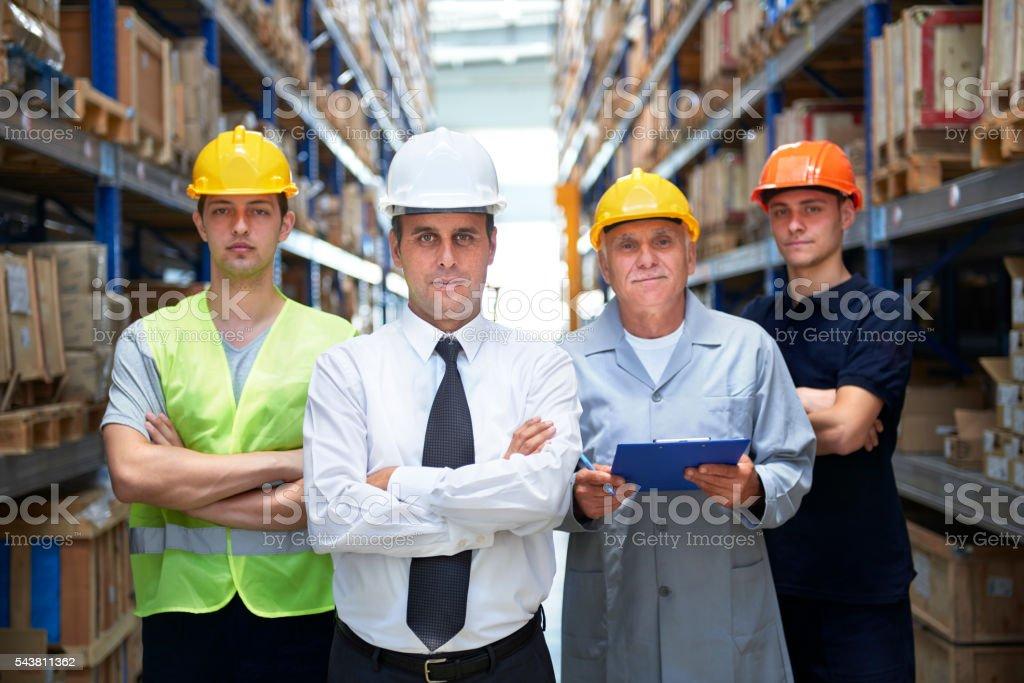 Manager and coworkers standing in warehouse aisle stock photo