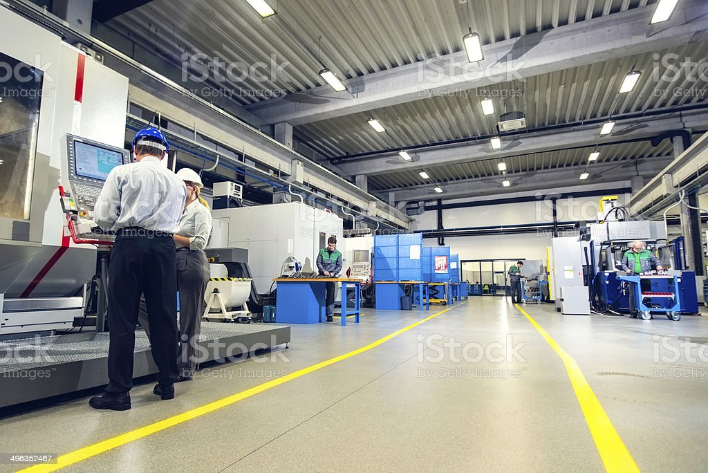 Manager and Female Engineer in the Factory Disscusing Project stock photo