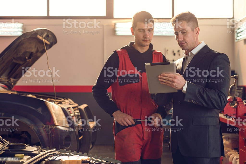 Manager and mechanic working on digital tablet in repair shop. stock photo