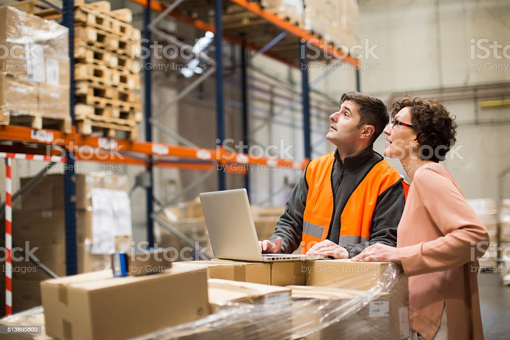 Manager and worker doing a checklist in the warehouse. stock photo