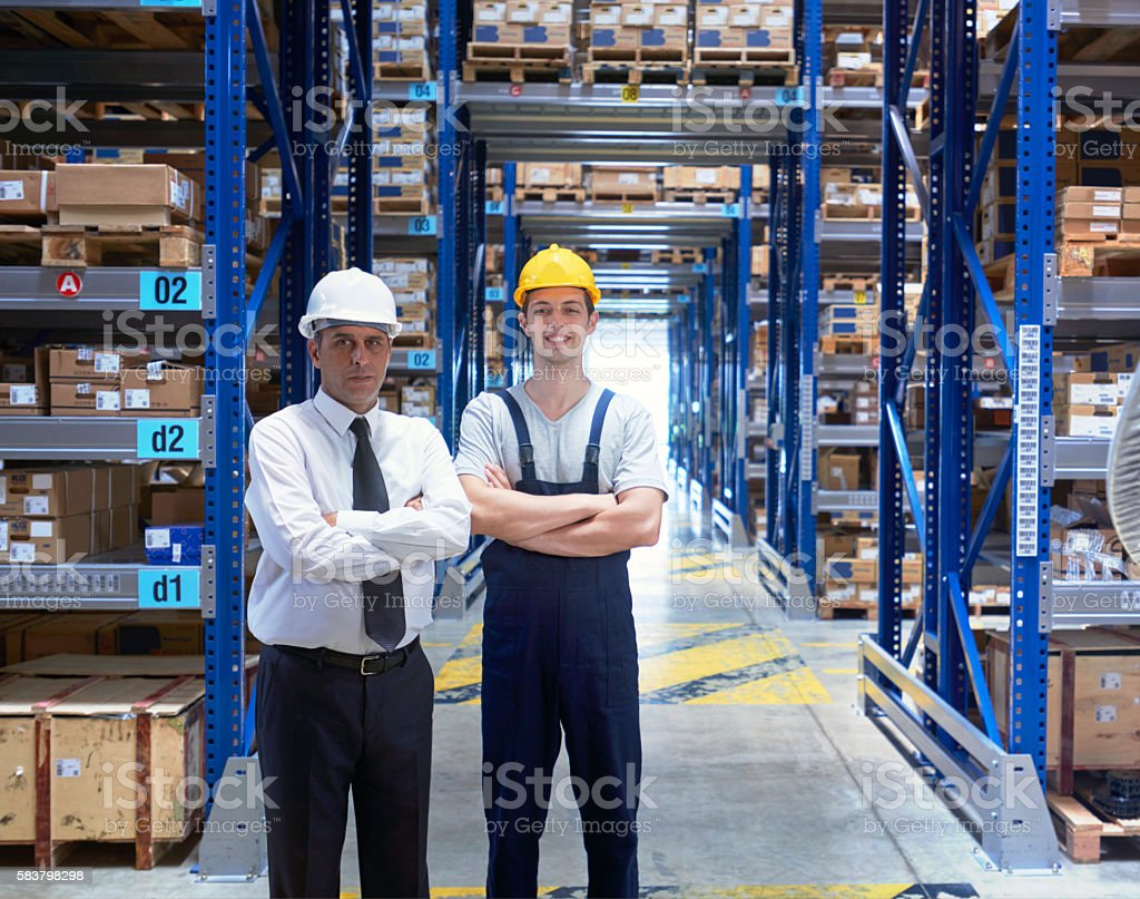 Manager and worker standing in warehouse aisle stock photo