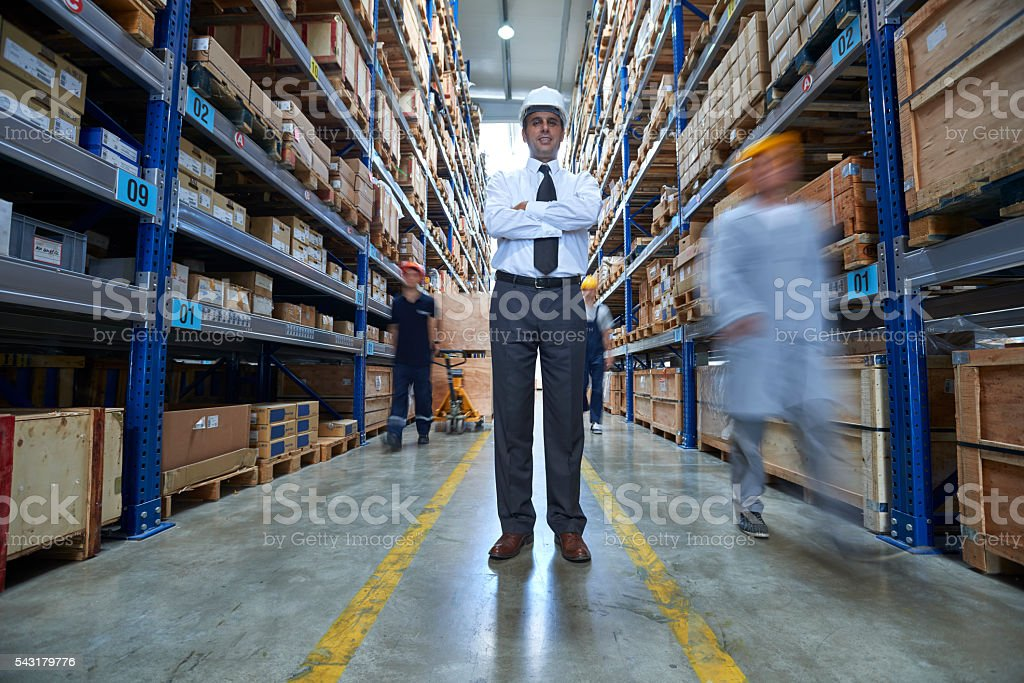 Manager and workers in warehouse aisle stock photo