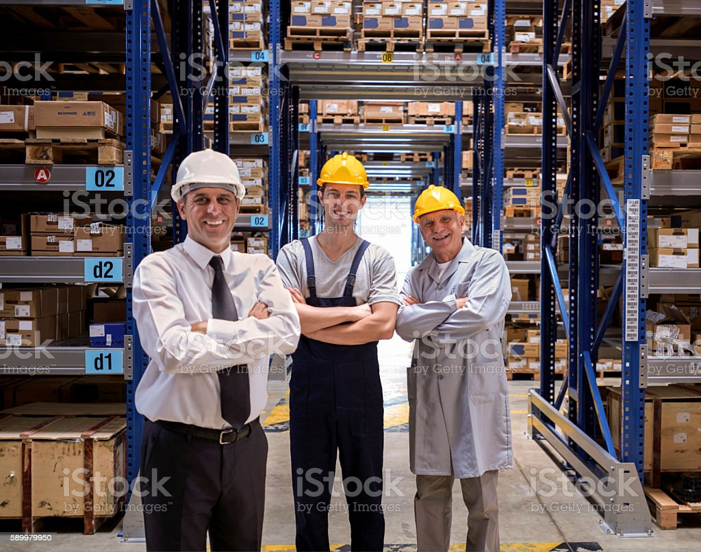 Manager and workers standing in warehouse aisle stock photo
