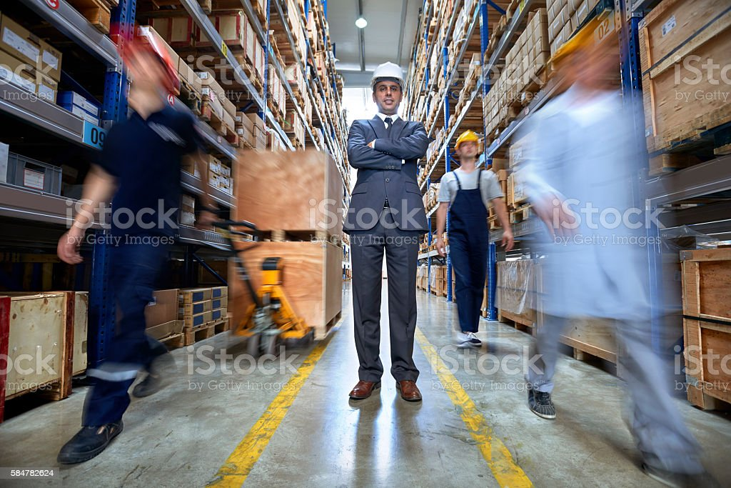 Manager and workers walkingin warehouse aisle stock photo