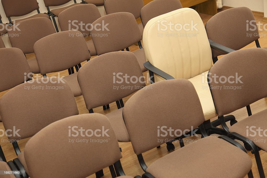 Manager chair among ordinary chairs royalty-free stock photo