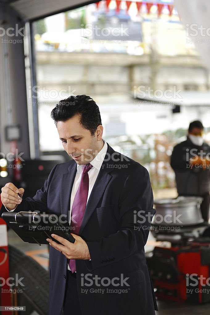 Manager checking supplies for car shop royalty-free stock photo