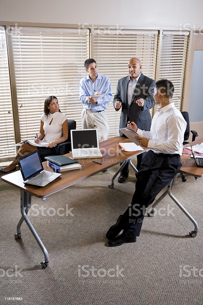 Manager directing three employees at meeting in office stock photo