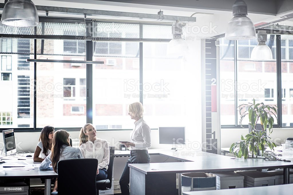 Manager discussing with executives in brightly lit office stock photo