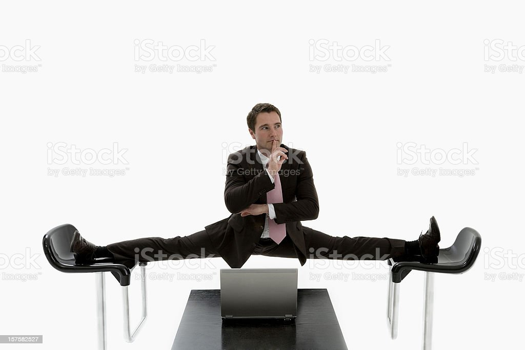 Manager doing a split between two black chairs in a suit stock photo