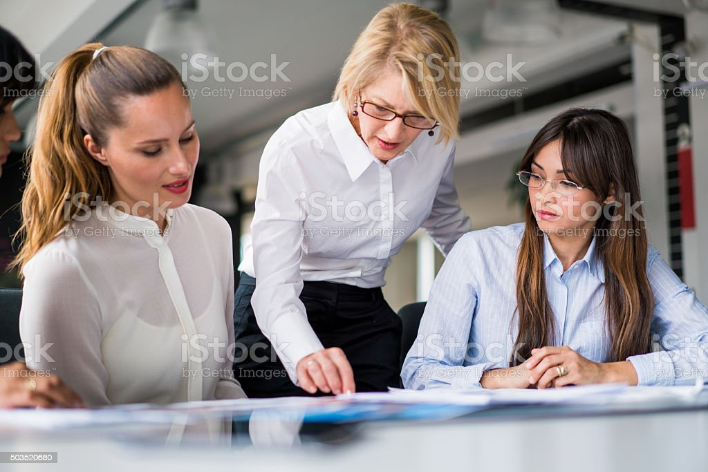 Manager explaining strategy to executives at desk stock photo