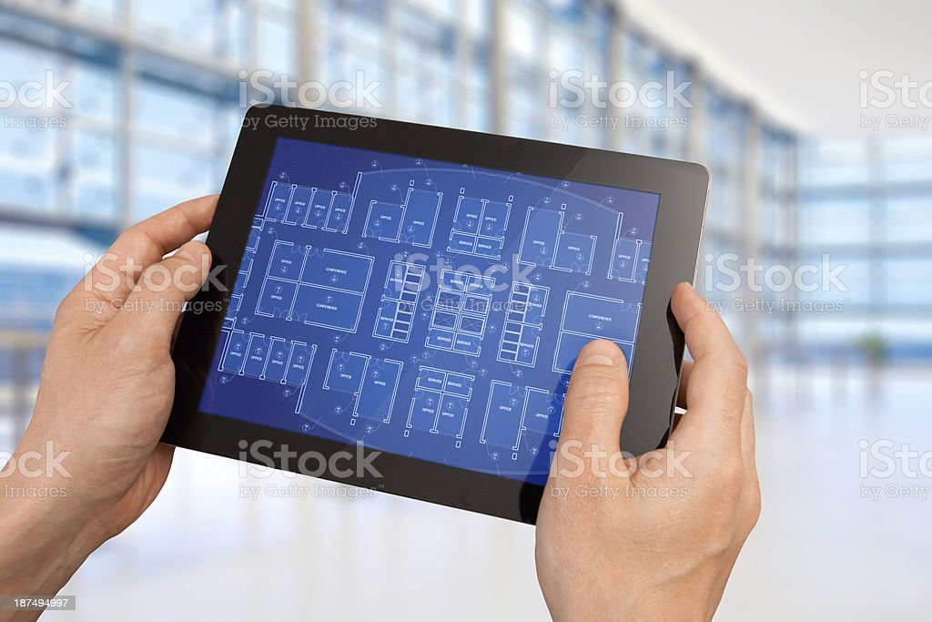 Manager holding interactive tablet showing an office architecture building project stock photo