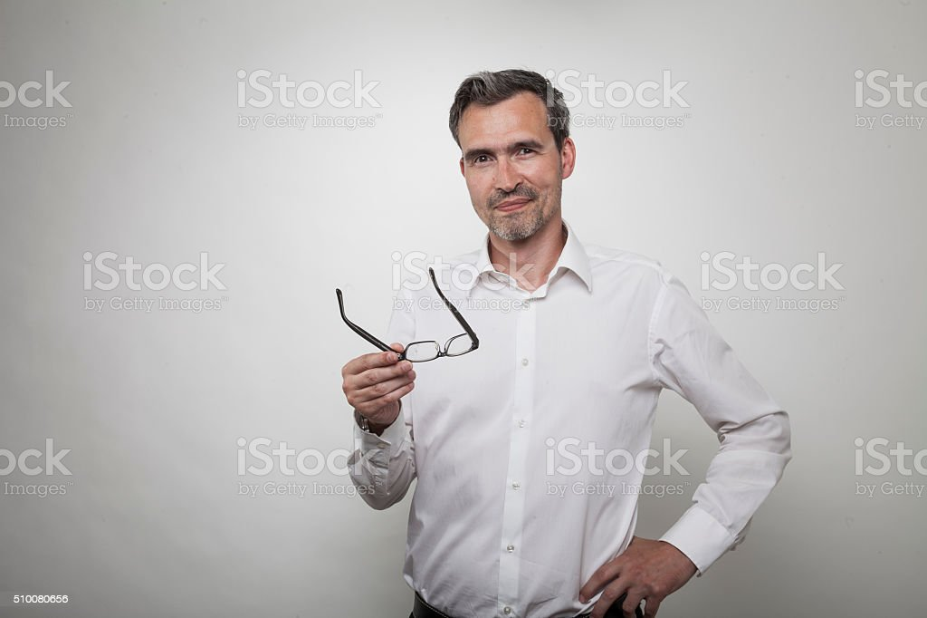 manager holds his glasses while smartly smiling at you stock photo