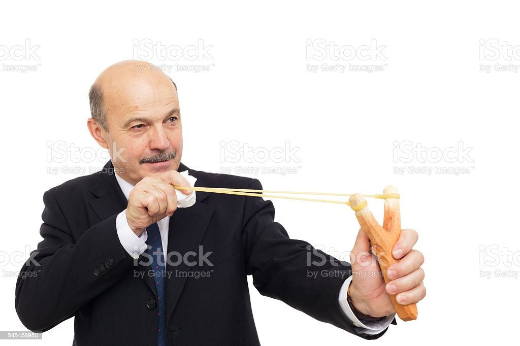 Manager in a suit playing shooting with slingshot stock photo