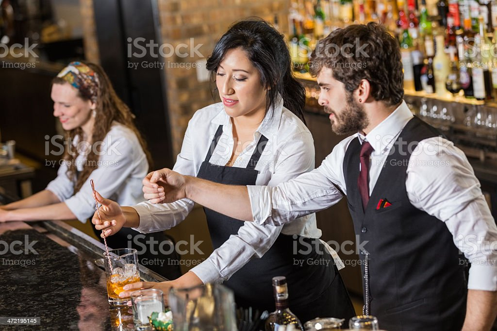 Manager in bar training new bartender to make mixed drinks stock photo