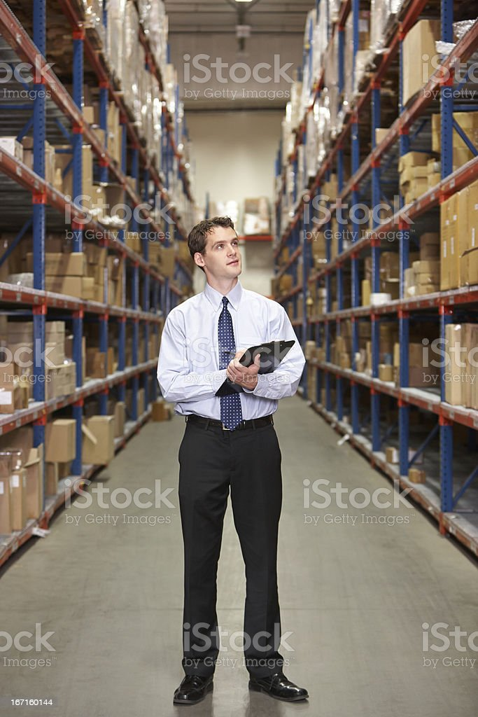 Manager In Warehouse With Clipboard royalty-free stock photo
