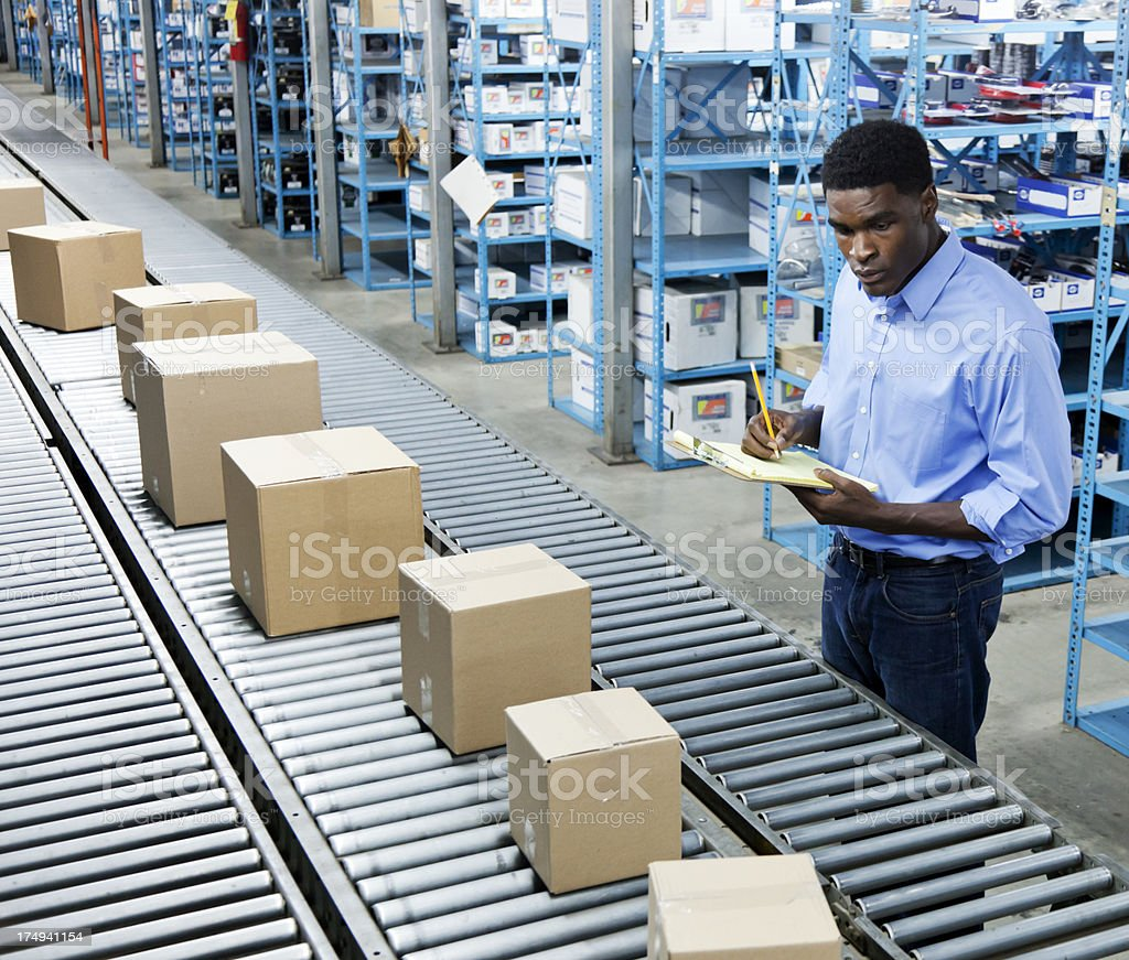 Manager Inspecting Boxes on a Conveyor Belt stock photo