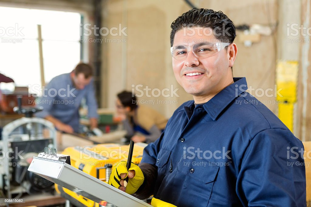 Manager of machine shop smiling while checking customer orders stock photo