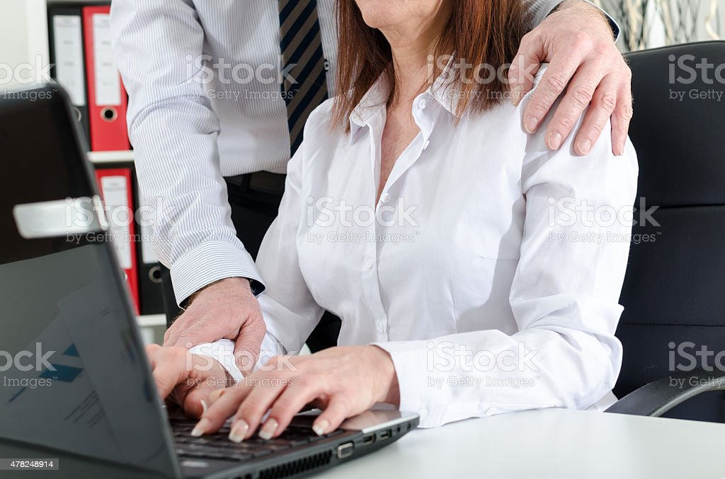 Manager putting his hand on the shoulder of his secretary stock photo
