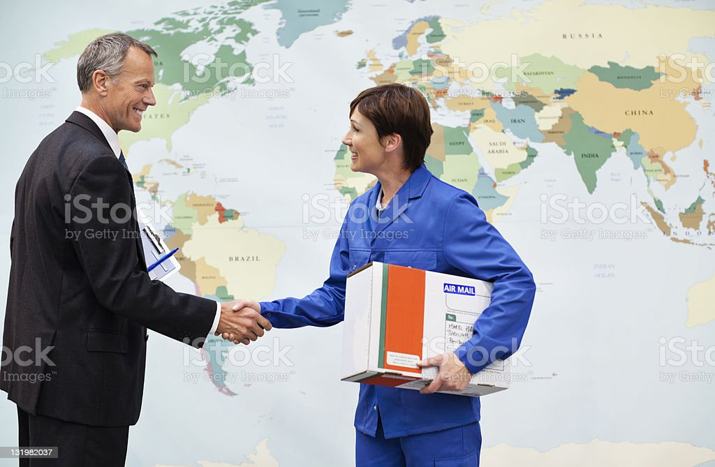 Manager shaking hands in front of world map stock photo