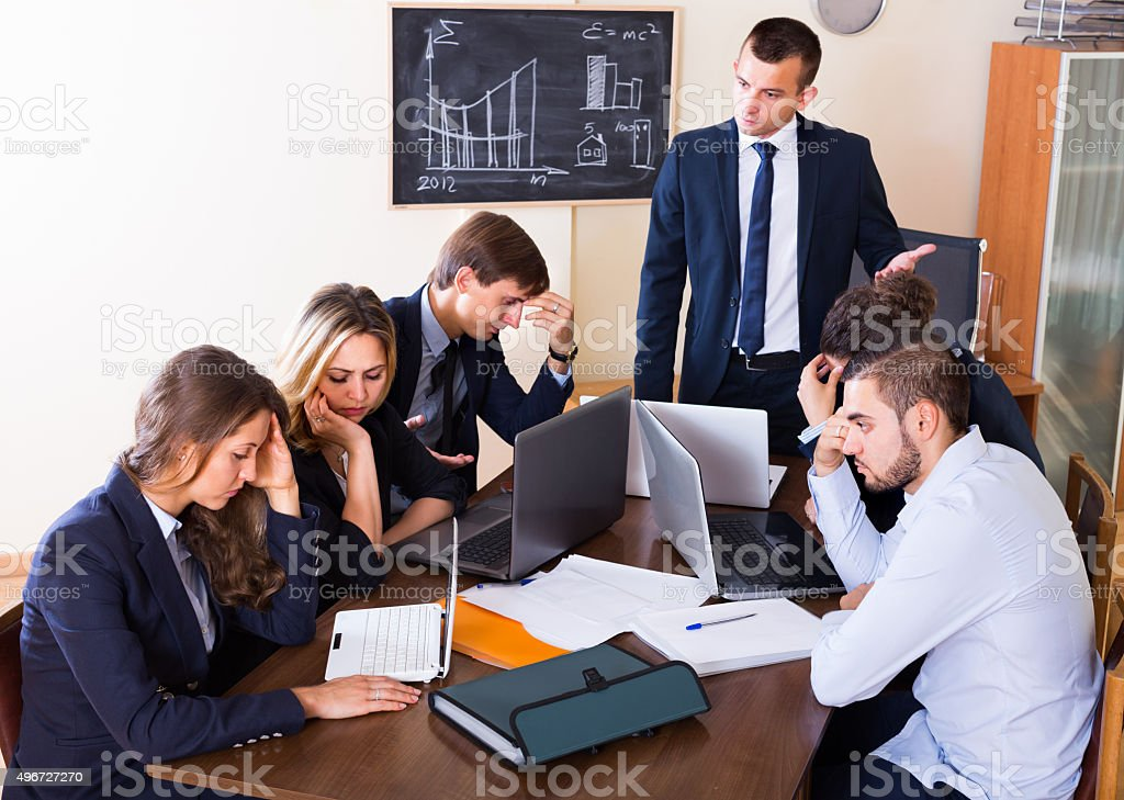Manager shouting to employees at group meeting stock photo