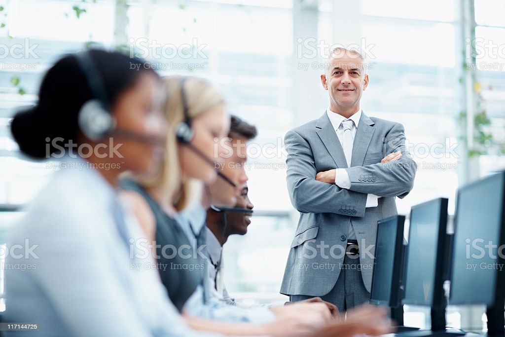 Manager standing in call center with team working royalty-free stock photo