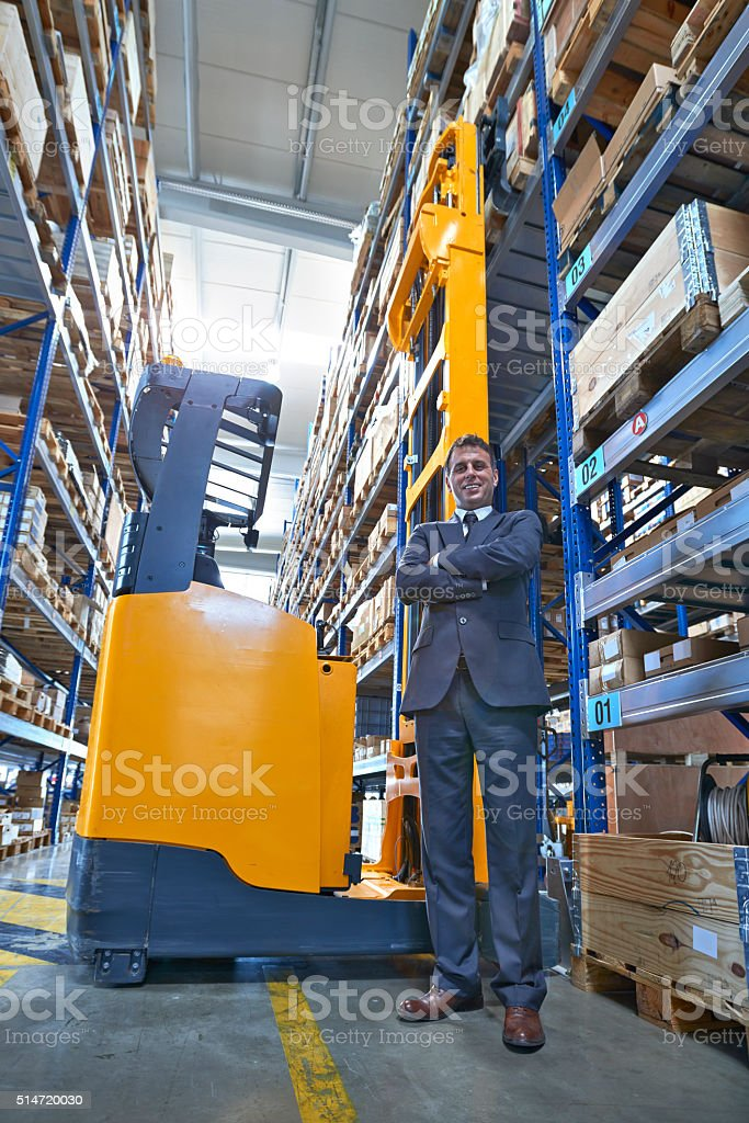 Manager standing in warehouse aisle stock photo