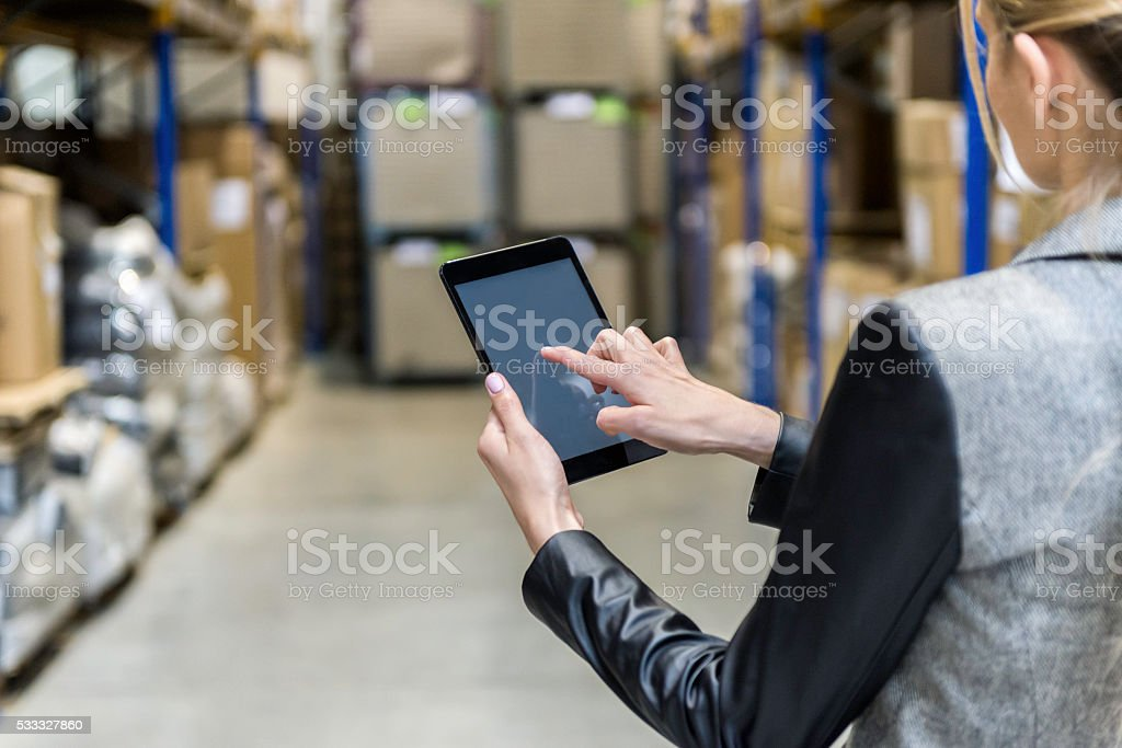 Manager touching tablet screen in warehouse stock photo