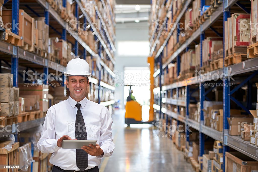 Manager using digital tablet in warehouse aisle stock photo