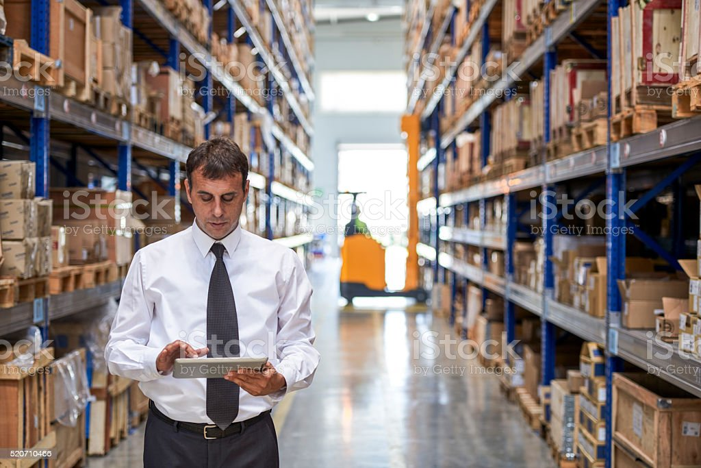 Manager using digital tablet in warehouse stock photo