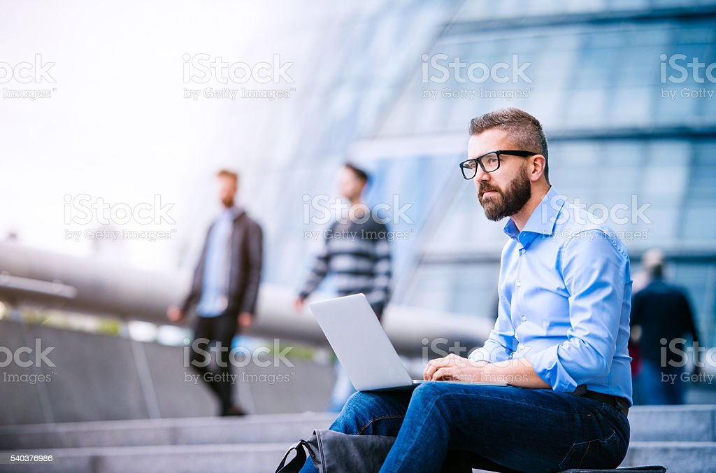 Manager with laptop, sitting on stairs, London, City Hall stock photo