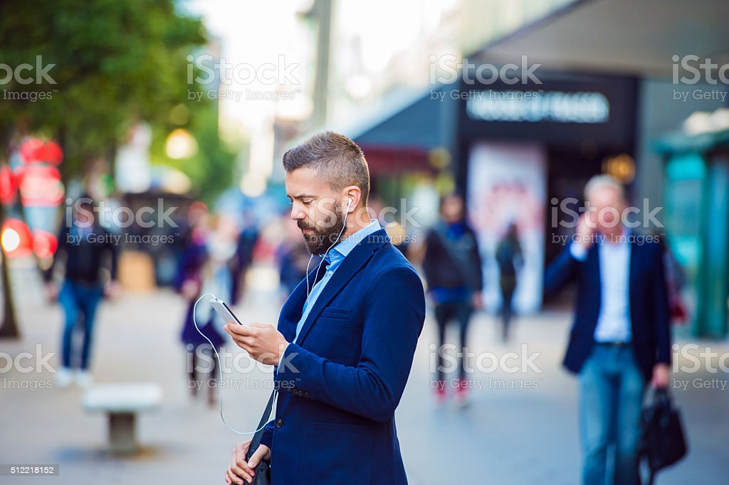 Manager with smartphone listening music outside in the street stock photo
