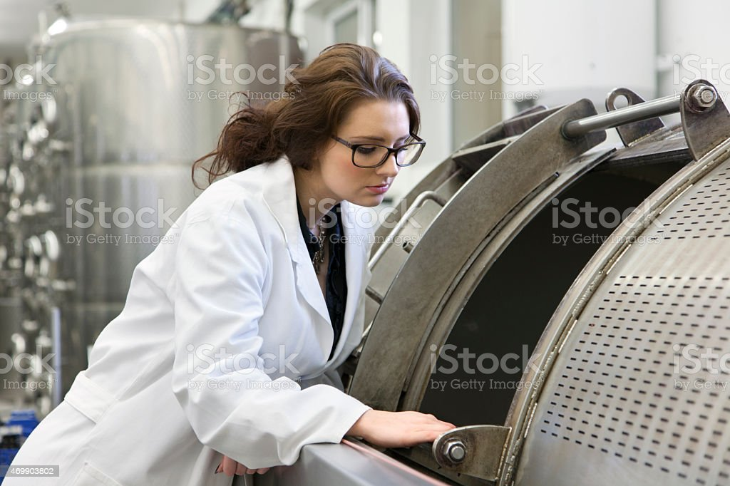 Manageress checks status of press on the vine stock photo