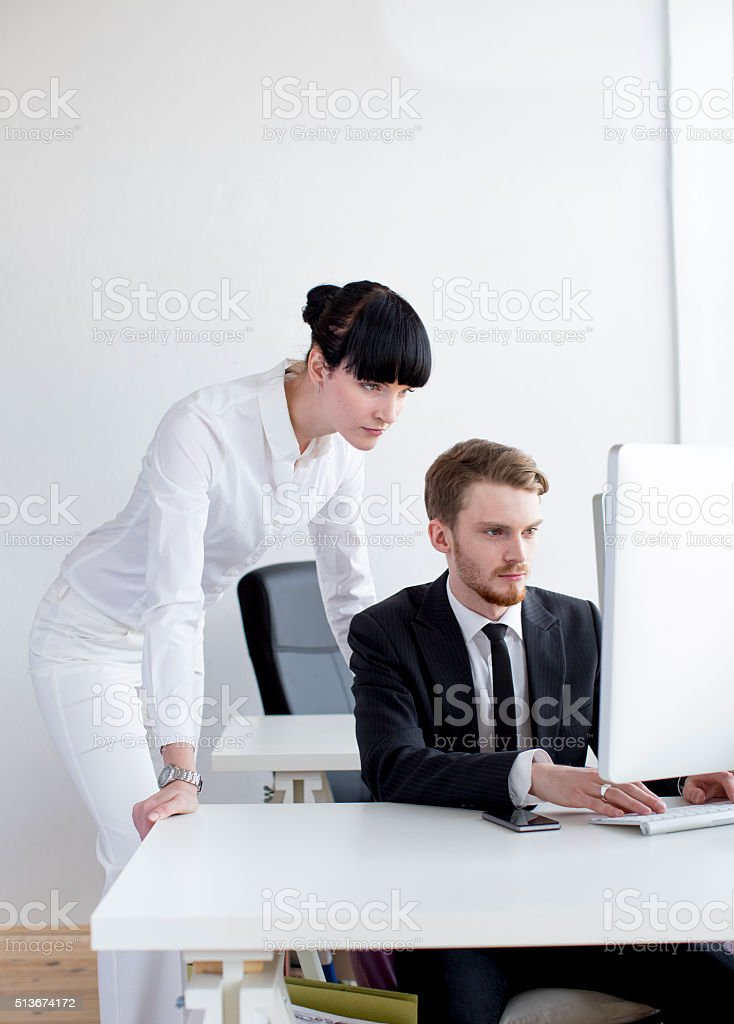 Managing Female Director Guiding Young Male Employee stock photo