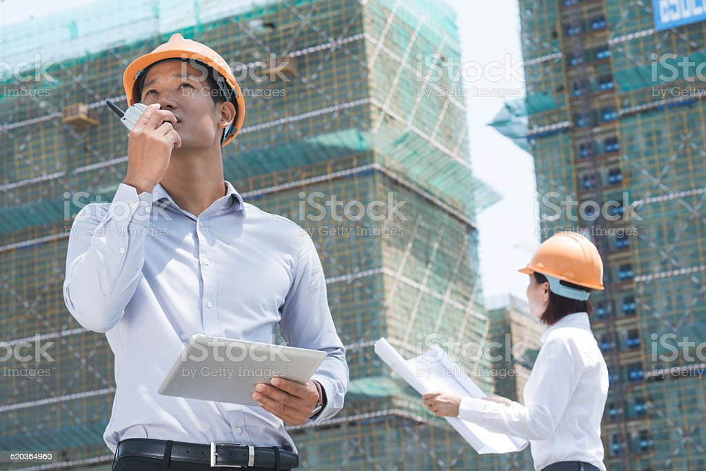 Managing work at construction site stock photo