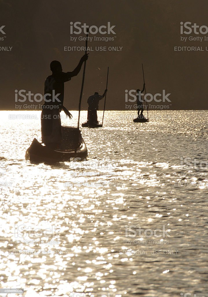 Manambolo River, Madagascar: silhouettes of men in canoes royalty-free stock photo