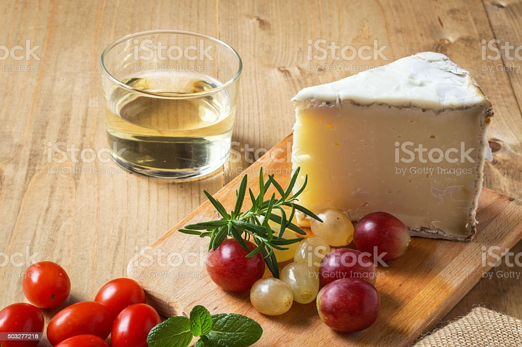Manchego cheese with grapes, mint and rosemary stock photo