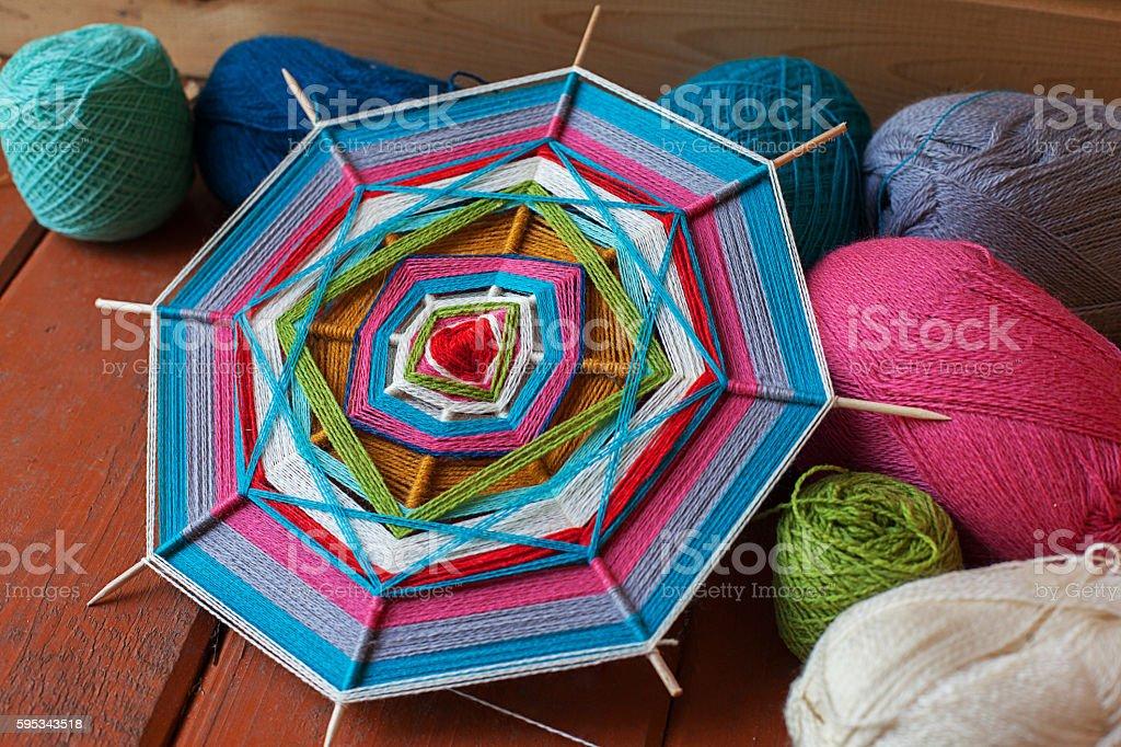 mandala on the wooden skewers sneedlework, wool, yarn stock photo