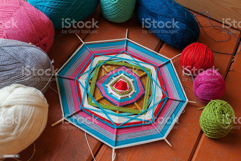 mandala on the wooden skewers spokes thread wool different colors stock photo