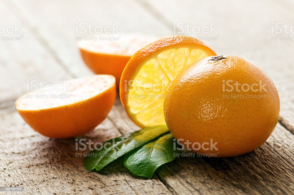 Mandarin oranges cut up on a wood table stock photo