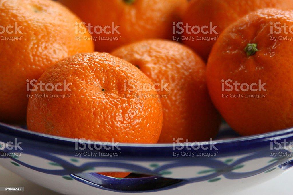 mandarin oranges in blue dish close-up stock photo